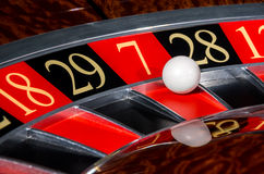 Classic casino roulette wheel with red sector seve. N 7 and white ball and sectors 18, 29, 28, 12 stock photos