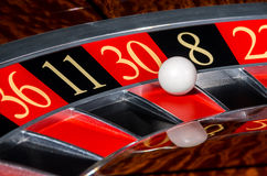 Classic casino roulette wheel with red sector thirty 30. And white ball and sectors 36, 11, 8, 22 stock photo