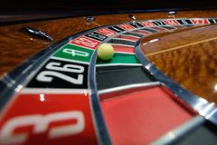 Classic casino roulette wheel with ball on number 0 green. A classic casino roulette wheel spinning with ball stopped on number 0 green close-up shot Stock Photography
