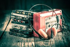 Classic cassette tape with headphones and walkman. Closeup of classic cassette tape with headphones and walkman royalty free stock photos