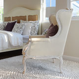Classic chair with brown pillow on carpet in vintage style bedroom Stock Photography