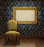 Classic chair and frame. Classic antique chair and gold plated frame in room with blue damask pattern wall royalty free stock images