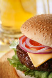 Classic cheeseburger with beer on background Royalty Free Stock Photo