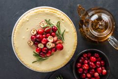 Classic cheesecake with cranberries and rosemary on a dark background. Winter version of cheesecake. Christmas. Classic cheesecake with cranberries and rosemary royalty free stock photography