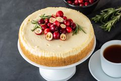 Classic cheesecake with cranberries and rosemary on a dark background. Winter version of cheesecake. Christmas. Classic cheesecake with cranberries and rosemary stock photography