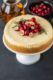 Classic cheesecake with cranberries and rosemary on a dark background. Winter version of cheesecake. Christmas. Classic cheesecake with cranberries and rosemary stock photo
