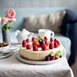 Classic cheesecake with fresh berries on the gray plate at table. Concept of healthy organic summer dessert royalty free stock photography