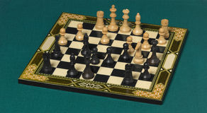 Classic chessboard with pieces over a green background Royalty Free Stock Images