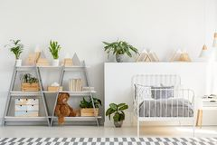 A classic child bedroom interior with simple, scandinavian style furniture and a gray wooden bookcase with a teddy bear. Concept stock image