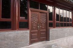 Classic Chinese wooden doors. A wooden door near a large Chinese wall -  Beijing 2016 Stock Photo