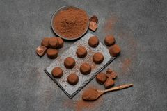 Classic chocolate truffles and cocoa powder on dark concrete background. Or table royalty free stock photography