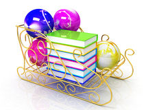 Classic Christmas balls and colorful book. On gold sledge on white background Stock Photography