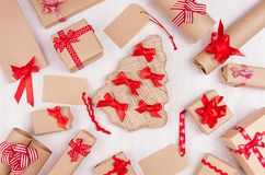 Classic christmas design of decoration - gift boxes of kraft paper with bright red bows and ribbons, tree on soft white wood table royalty free stock image