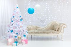 Classic Christmas light interior in white, pink and blue tones with a couch, tree and molding Royalty Free Stock Images
