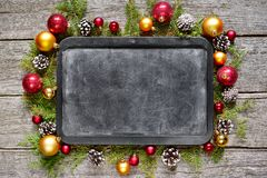 Classic christmas and new year composition chalk board, balls, toys, candy, fir branches on vintage wooden background Stock Images