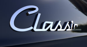 Classic Chrome Car Emblem. A closeup view of the word classic writting as a chrome emblem in a retro font set on a car painted in reflective black paint Stock Photos