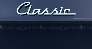 Classic Chrome Car Emblem. A closeup view of the word classic writting as a chrome emblem in a retro font set on a car painted in reflective black paint Royalty Free Stock Photography