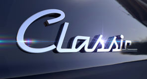 Classic Chrome Car Emblem. A closeup view of the word classic writting as a chrome emblem in a retro font set on a car painted in reflective black paint royalty free stock image