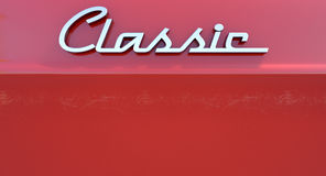Classic Chrome Car Emblem. A closeup view of the word classic writting as a chrome emblem in a retro font set on a car painted in reflective red paint Royalty Free Stock Images