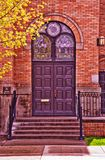 Classic church doors in brick wall. Classice church doors with stain glass windows above in a brick wall with steps and iron rails Stock Photo