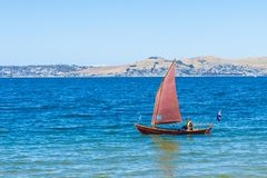 Classic clinker sailing dinghy with red sail stock photography