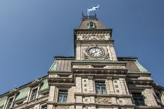 Classic clocktower building Quebec City Canada with flag of quebec on a sunny day blue sky royalty free stock image