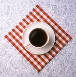 Classic Coffee. Coffee cup and saucer on a napkin on a patterened tablecloth Stock Images