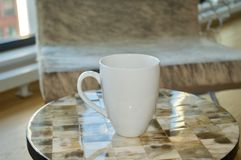 Classic Coffee Mug Resting on Tiled Table royalty free stock photography