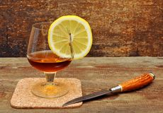 Classic cognac with lemon and knife Stock Image