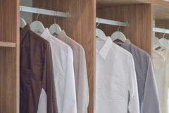Classic color shirts hanging in wooden wardrobe Stock Image