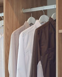 Classic color shirts hanging in wooden wardrobe Stock Images