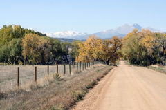 Classic Colorado Scene. A dirt road, fence line, and a scenic view of Long's Peak in the Fall compose a classic image of Colorado royalty free stock image