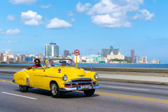 Classic convertible car on the malecon avenue in Havana. HAVANA,CUBA - JULY 14,2016 : Old convertible car on the Havana malecon avenue with a view of the sea and Royalty Free Stock Photo