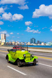 Classic convertible car on the malecon avenue in Havana. HAVANA,CUBA - JULY 14,2016 : Old convertible car on the Havana malecon avenue with a view of the sea and Royalty Free Stock Photography