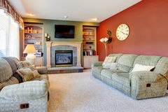 Classic cozy living room interior with fireplace and red wall. Stock Photos