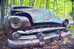 Classic Decay. An old car is abandoned among the trees Royalty Free Stock Photography