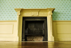 Classic decor. A classic fireplace in an elegant part panelled room royalty free stock photos