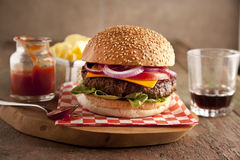 Classic deluxe cheeseburger with lettuce, onions, tomato and pickles on a sesame seed bun Stock Images