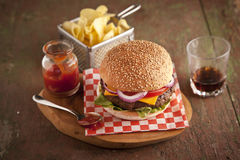 Classic deluxe cheeseburger with lettuce, onions, tomato and pickles on a sesame seed bun. Stock image Stock Photography