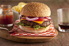 Classic deluxe cheeseburger with lettuce, onions, tomato and pickles on a sesame seed bun. Stock image Stock Photo
