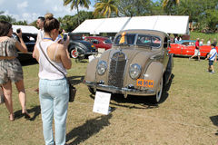 Classic desoto on field. Classic American car on golf course grounds. 1935 Desoto airflow at 2014 boca raton concours delegance with people about and girl taking Royalty Free Stock Photo