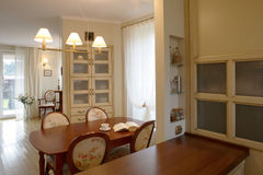Classic Dining Room. A view of an open, spacious, modern apartment dining room with table, chairs and built in china cabinet as seen from the kitchen royalty free stock images