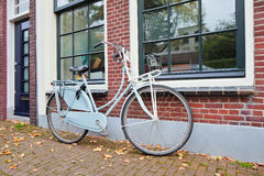 Classic Dutch bicycle parked against brick house in autumn, Gouda, Netherlands Royalty Free Stock Images