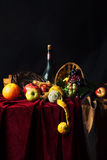 Classic Dutch still life with dusty bottle of wine and fruit on a dark background Stock Images