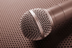 Classic dynamic microphone. On background  perforated. Toned Stock Photo