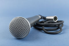 Classic dynamic microphone. On a blue  background Royalty Free Stock Photography