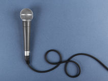 Classic dynamic microphone. On a blue  background Stock Photos