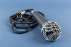 Classic dynamic microphone. On a blue  background Stock Photography