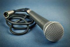Classic dynamic microphone. On a blue  background. Toned Stock Photo