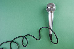 Classic dynamic microphone. On a green background Royalty Free Stock Image